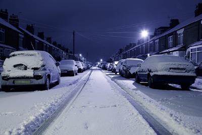 Autot kadun varrella lumen peitossa