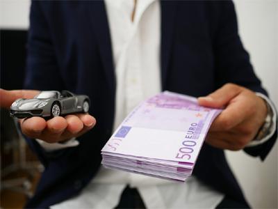 Auto ja rahatukku kädessä